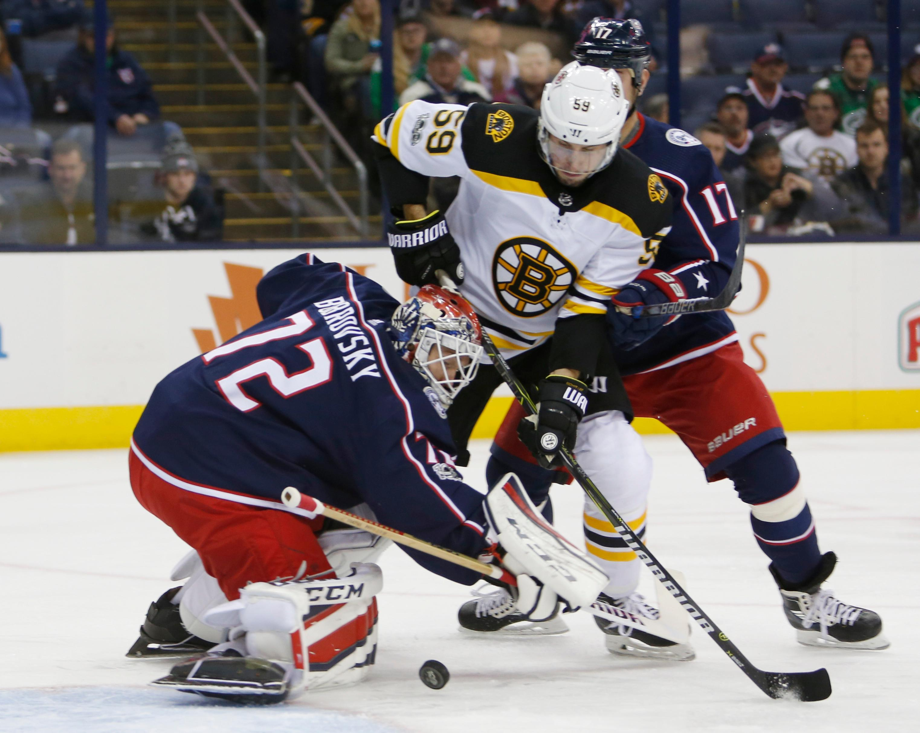 Columbus Blue Jackets' Sergei Bobrovsky, left, of Russia, makes a save as teammate Brandon Dubinsky, right, and Boston Bruins' Tim Schaller fight for position during the first period of an NHL hockey game Monday, Oct. 30, 2017, in Columbus, Ohio. (AP Photo/Jay LaPrete)