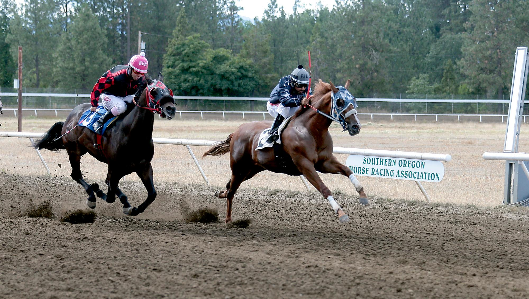 Larry Stauth Jr./For the Mail TribuneHarem Bar Cartel, with jockey Ruben Lozano, races past Arizona Favorite in the fifth race at Grants Pass Downs on Sunday.