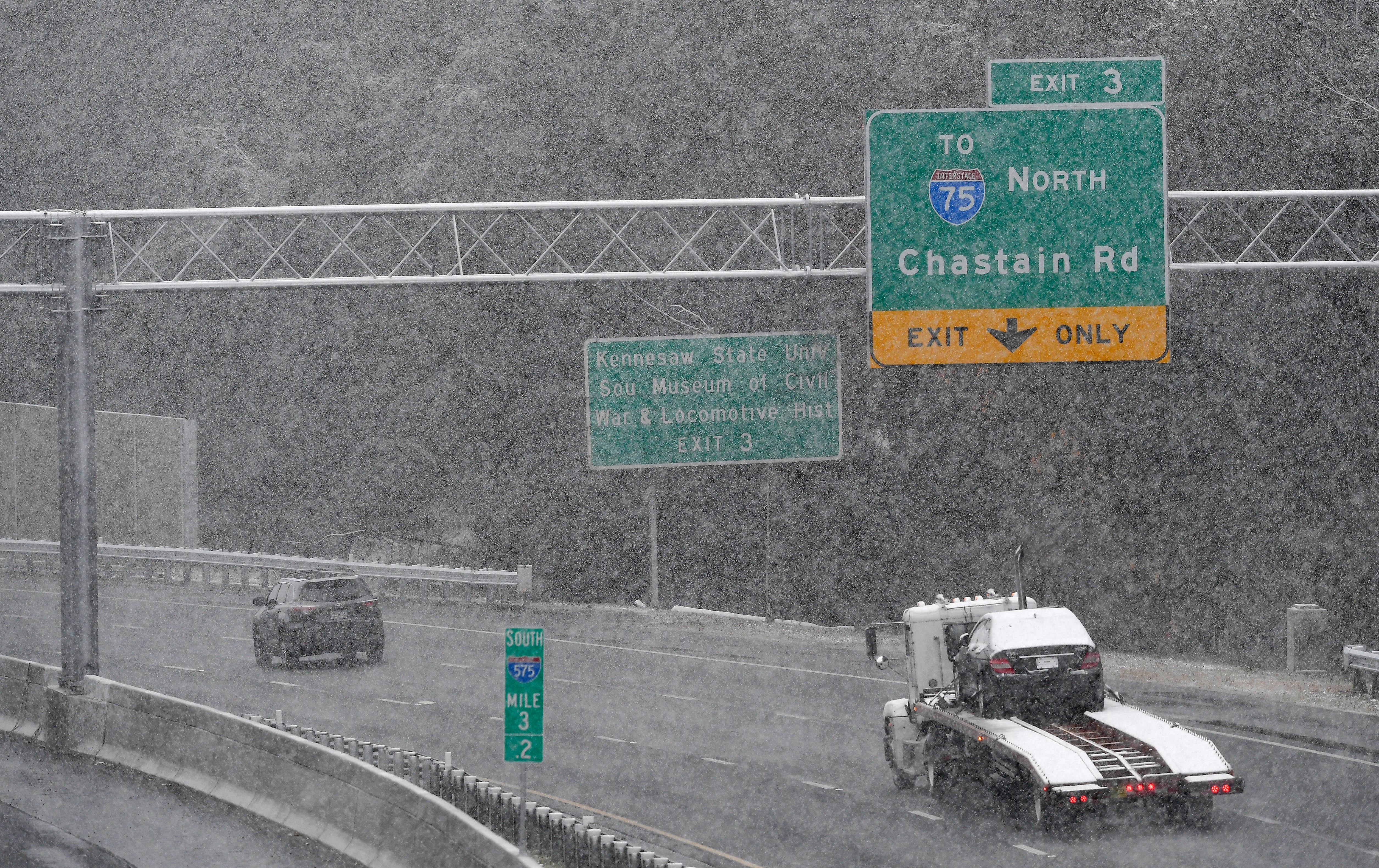 Traffic moves south in a moderate snow, Friday, Dec. 8, 2017, in Kennesaw, Ga. The forecast called for a wintry mix of precipitation across several Deep South states. (AP Photo/Mike Stewart)