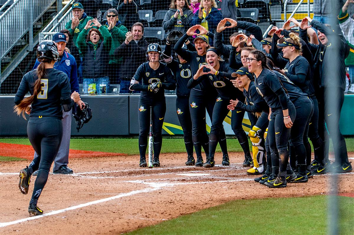 The Duck's Nikki Udria (#3) runs in to her team surrounding home upon scoring a home run. The Oregon Ducks defeated the Cal Golden Bears 2-1 in the second game of the three game series. Photo by August Frank, Oregon News Lab