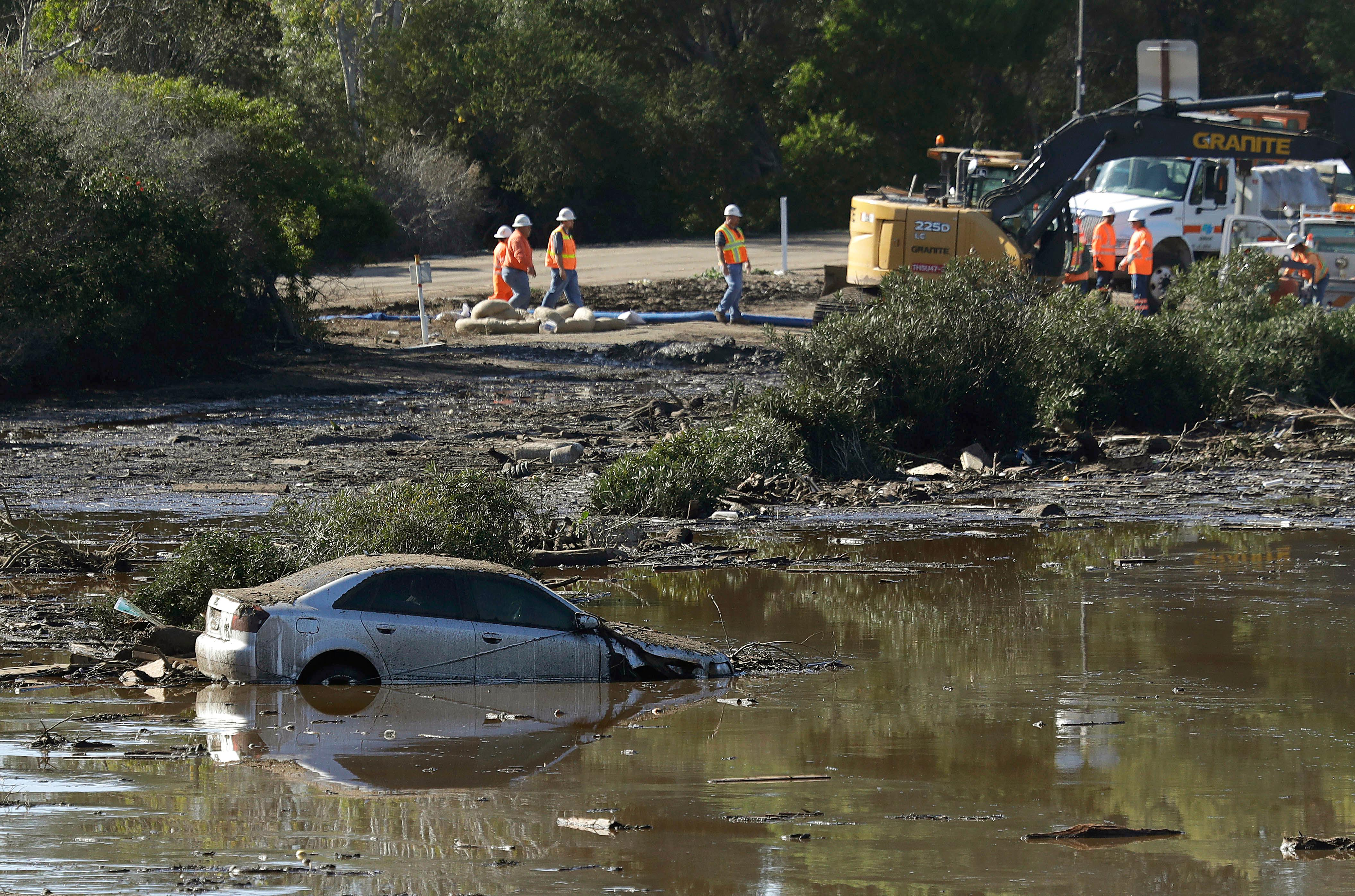 A car sits stranded in flooded water in Montecito, Calif., Wednesday, Jan. 10, 2018. Dozens of homes were swept away or heavily damaged and several people were killed Tuesday as downpours sent mud and boulders roaring down hills stripped of vegetation by a gigantic wildfire that raged in Southern California last month. (AP Photo/Marcio Jose Sanchez)