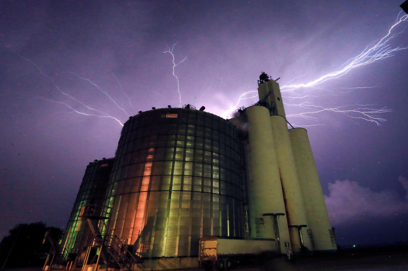 Lightning from a severe storm fills the sky behind a grain elevator in