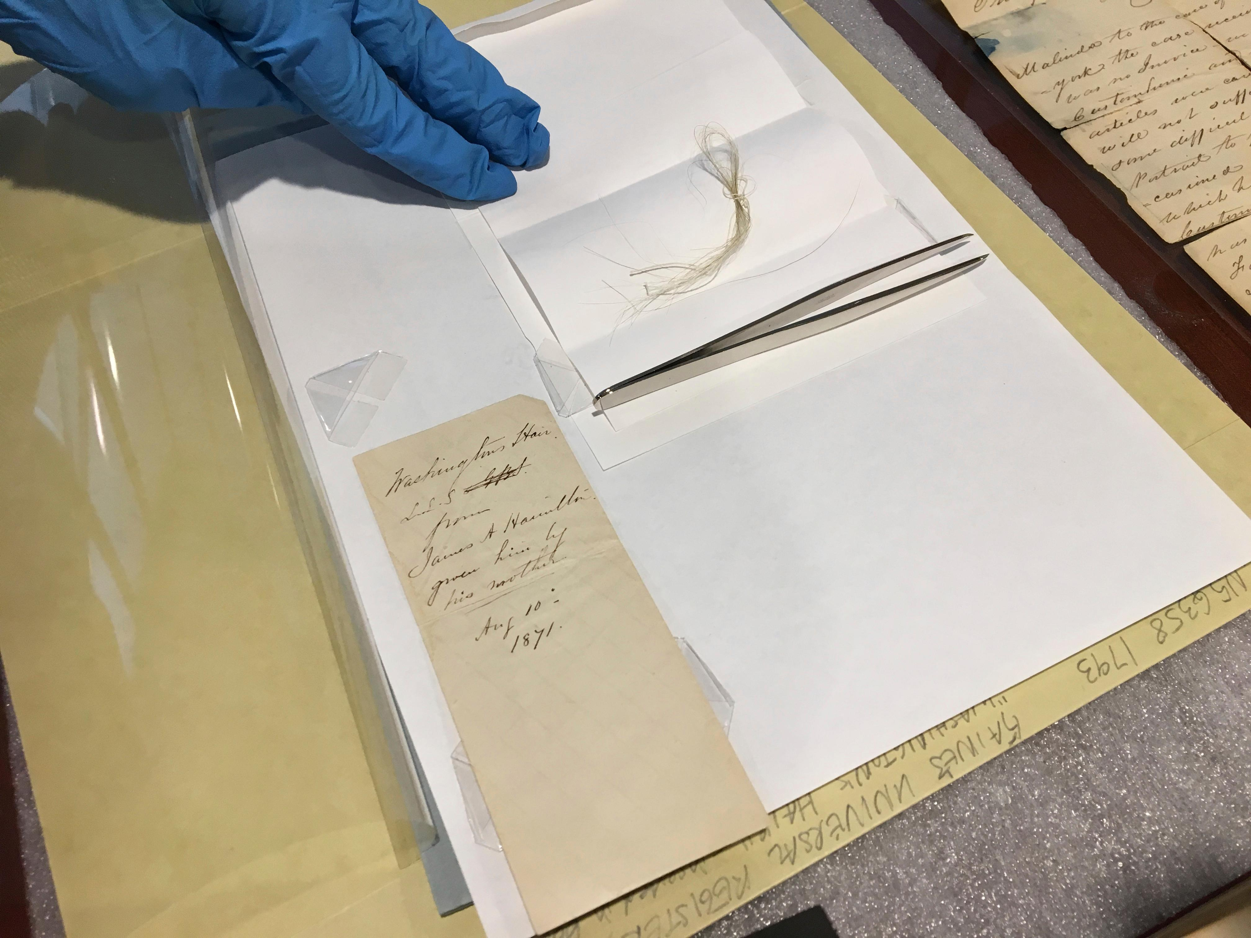 In this Feb. 14, 2018 photo, a lock of George Washington's hair and the envelope that contained it are seen on a table in the Union College library in Schenectady, N.Y. John Myers, the college's catalog and metadata librarian, discovered the hair strands in a yellowed envelope he'd found in a grimy old leather-bound almanac in the school's archives. (AP Photo/Mary Esch)