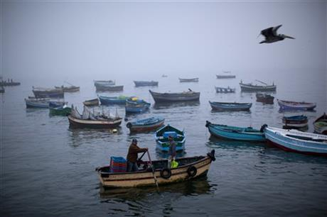Fishermen navigate their boat out of the Chorrillo dock in the Pacific Ocean waters of Lima, Peru, Wednesday, April 2, 2014.