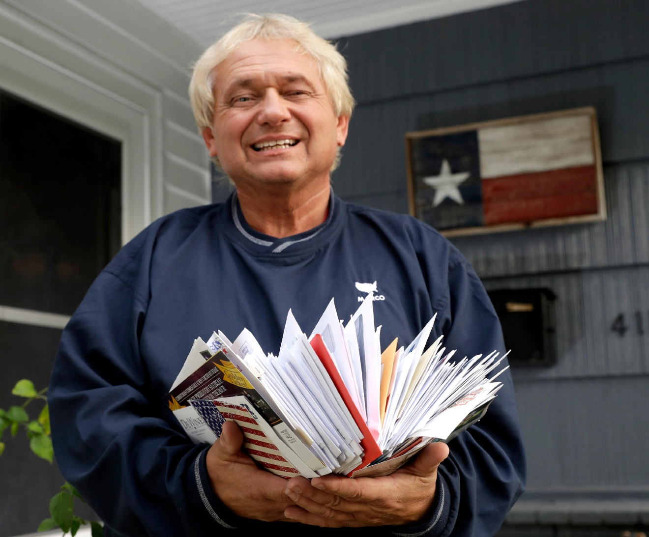 Rex Teter, a member of the Electoral College, holds two days of delivered mail at his home in Pasadena, Texas, Tuesday, Dec. 13, 2016. And you thought Election Day was in November. Electors are gathering in every state Dec, 19, to formally elect Donald Trump president even as anti-Trump forces try one last time to deny him the White House. Republican electors say they have been deluged with emails, phone calls and letters urging them not to support Trump. Many of the emails are part of coordinated campaigns. (AP Photo/David J. Phillip)
