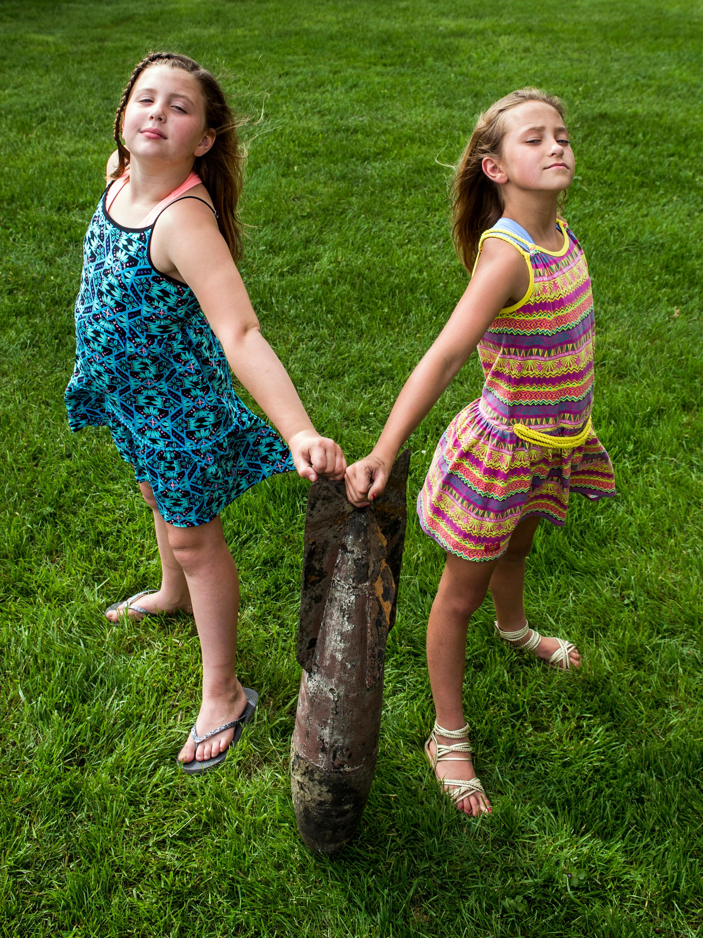In this Wednesday, May 30, 2018 photo, Paige Burnett, 10, left, and Sage Menzies, 9  pose with a World War I practice bomb they discovered the day before while swimming in Lobdell Lake behind the Menzies' home in Linden, Mich. The two found the bomb while pretending to be mermaids, and diving deep to search through the mucky lake bottom, when they found the tail end of the practice bomb. (Jake May/The Flint Journal via AP)