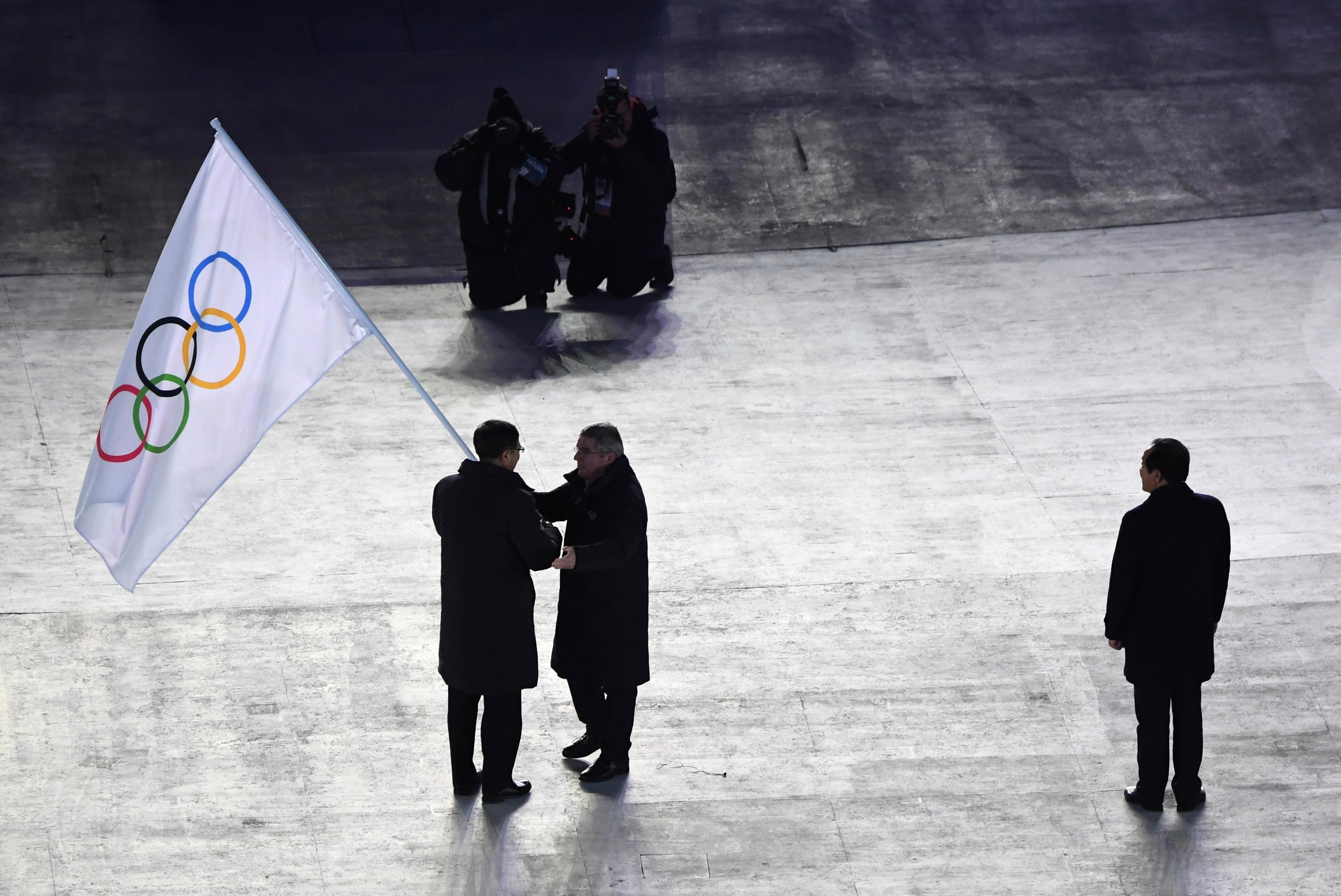 International Olympic Committee President Thomas Bach, center, hands the Olympic flag to the mayor of Beijing, China, Chen Jining, during the closing ceremony of the 2018 Winter Olympics in Pyeongchang, South Korea, Sunday, Feb. 25, 2018. Sim Jae-guk, the mayor of Pyeongchang, South Korea, is at right. (Florien Choblet/Pool Photo via AP)