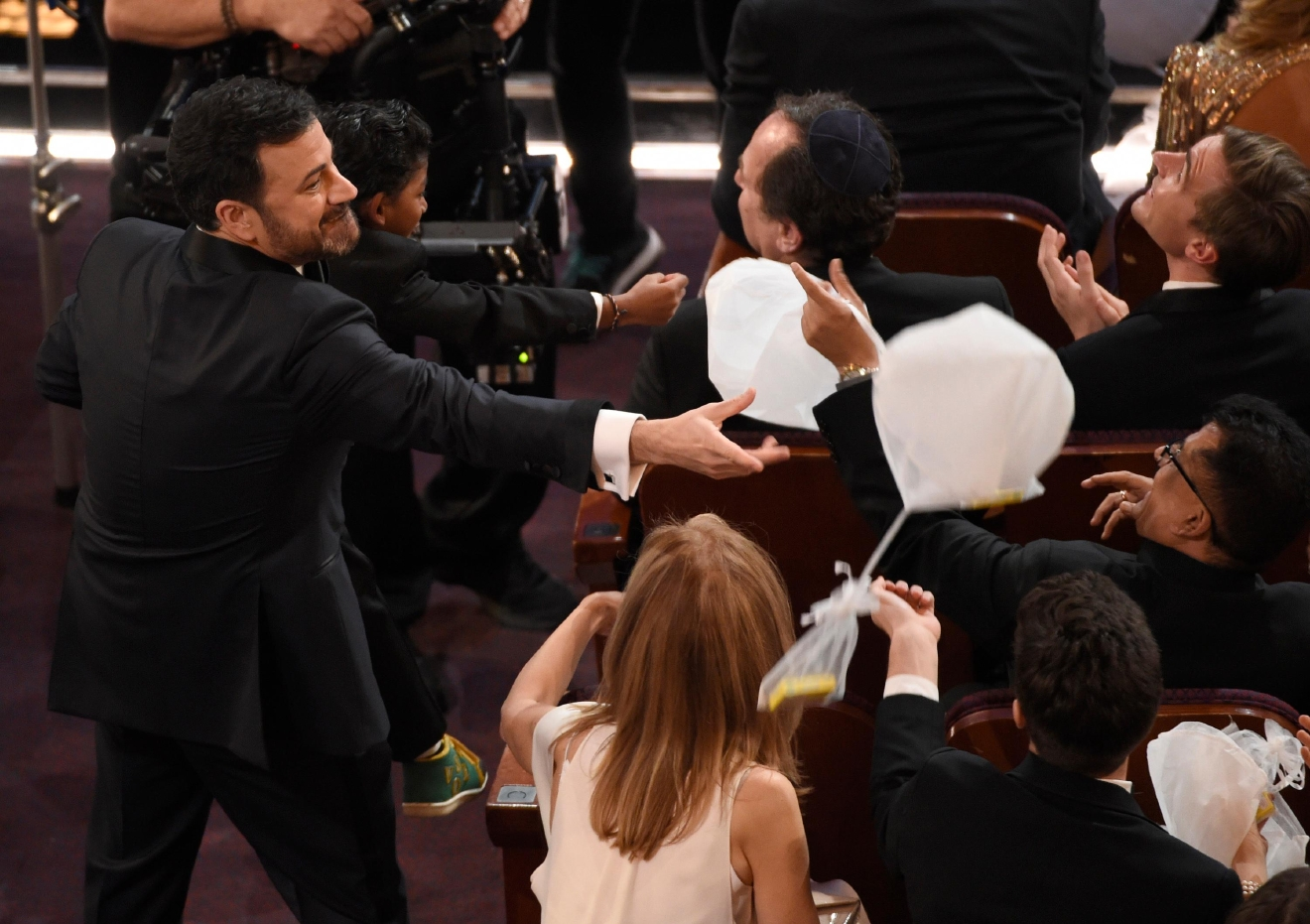 Host Jimmy Kimmel, left, raises Sunny Pawar as candy balloons fall on the audience at the Oscars on Sunday, Feb. 26, 2017, at the Dolby Theatre in Los Angeles. (Photo by Chris Pizzello/Invision/AP)