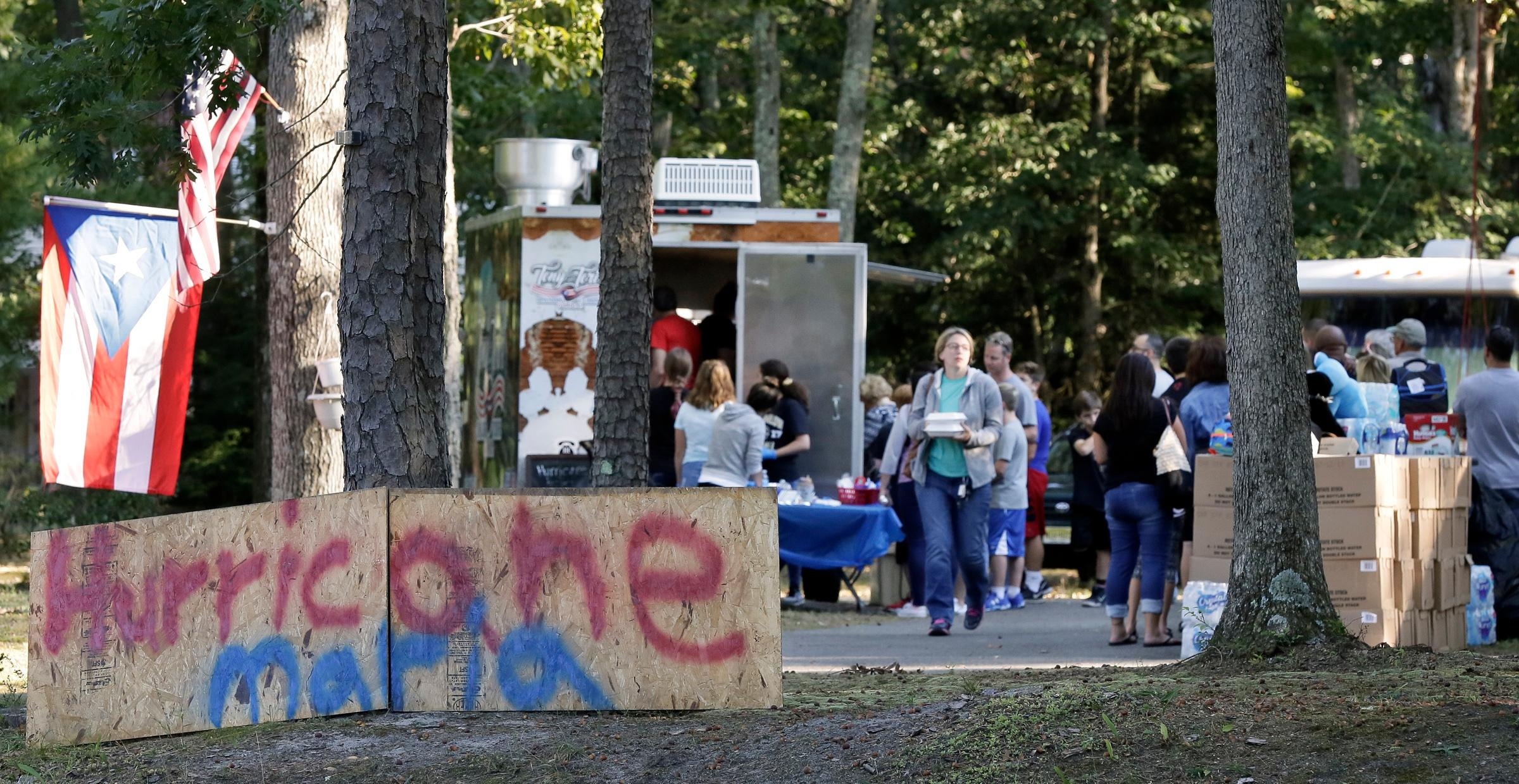 People participate in the food truck fundraiser for the people of Puerto Rico in the devastating aftermath of Hurricane Maria at Anthony Barber and Victoria Martinez-Barber's home, Friday, Sept. 29, 2017, in Medford, N.J. The couple teamed up with survivalist Joseph Badame whose multitude of stored food and supplies were donated to the victims of the hurricane.  (Elizabeth Robertson/The Philadelphia Inquirer via AP)
