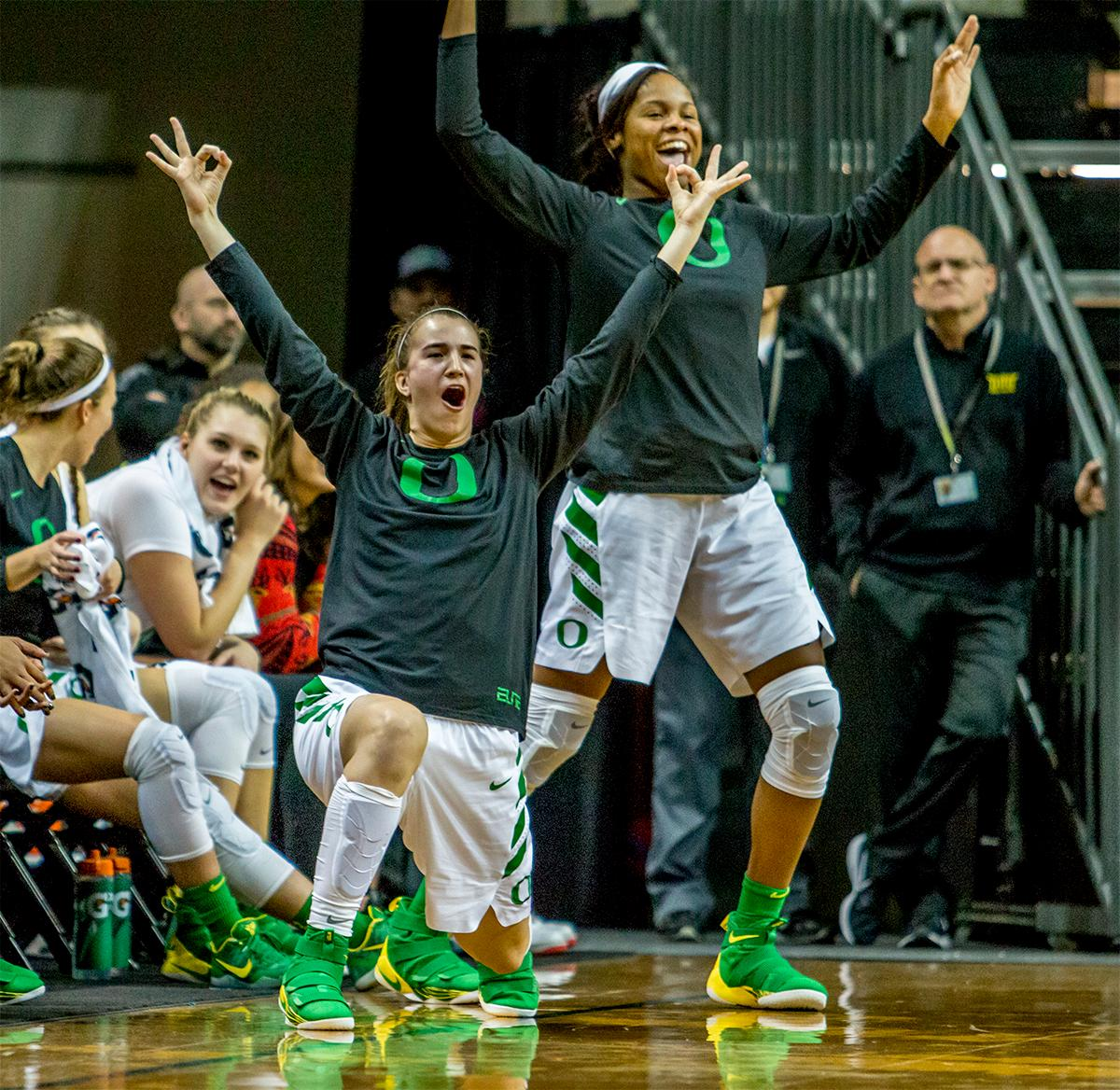 Ducks on the bench celebrate their team scoring a three pointer. The University of Oregon Ducks women basketball team defeated the Southern Utah Thunderbirds 98-38 in Matthew Knight Arena Saturday afternoon. The Ducks had four players in double-digits: Ruthy Hebard with 13; Mallory McGwire with 10; Lexi Bando with 17 which included four three-pointers; and Sabrina Ionescu with 16 points. The Ducks overwhelmed the Thunderbirds, shooting 50% in field goals to South Utah's 26.8%, 53.8% in three-pointers to 12.5%, and 85.7% in free throws to 50%. The Ducks, with an overall record of 8-1, and coming into this game ranked 9th, will play their next home game against Ole Miss on December 17. Photo by August Frank, Oregon News Lab