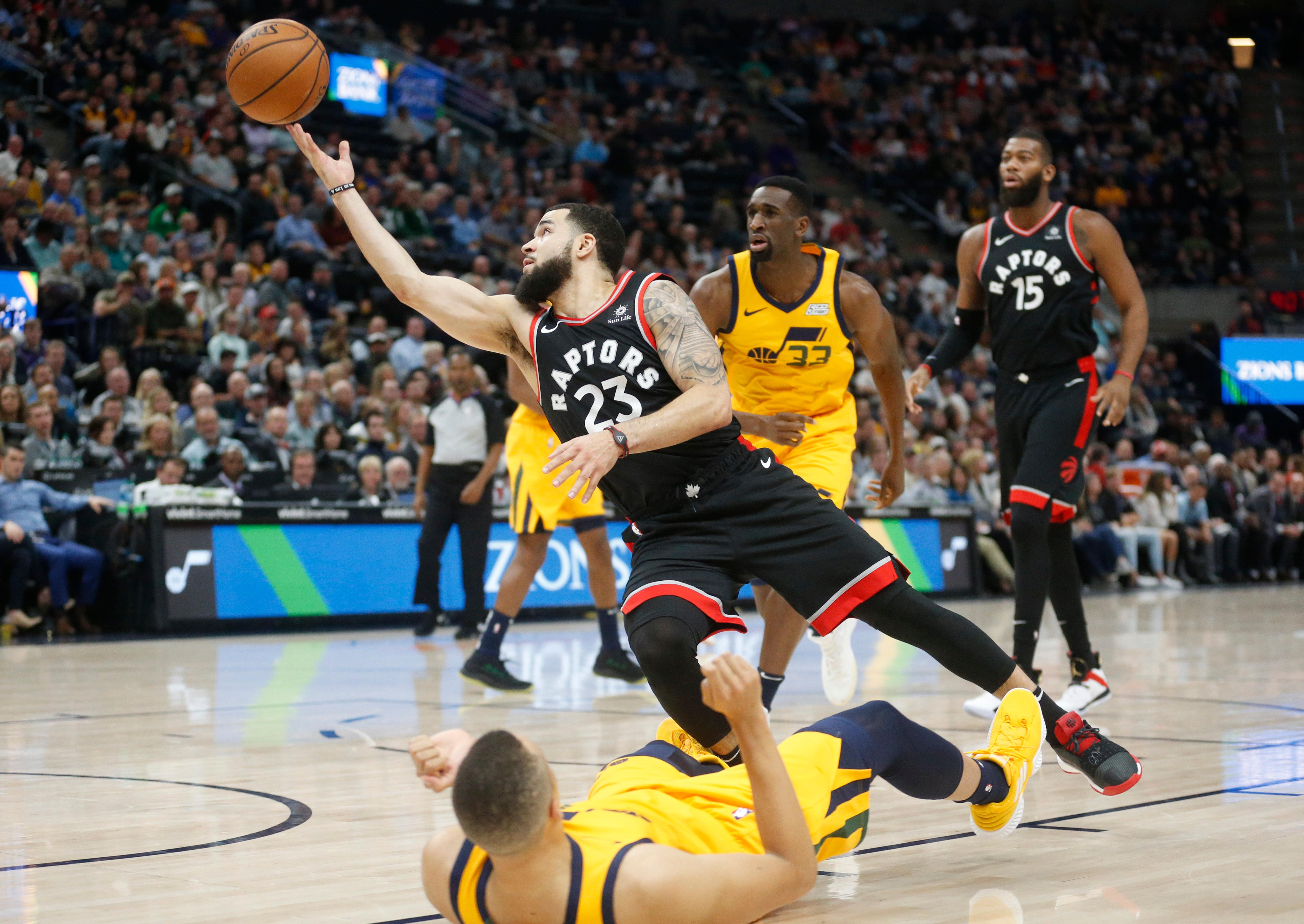 Toronto Raptors guard Fred VanVleet (23) lays the ball up as Utah Jazz guard Dante Exum, foreground, falls as he defends in the second half during an NBA basketball game Monday, Nov. 5, 2018, in Salt Lake City. (AP Photo/Rick Bowmer)