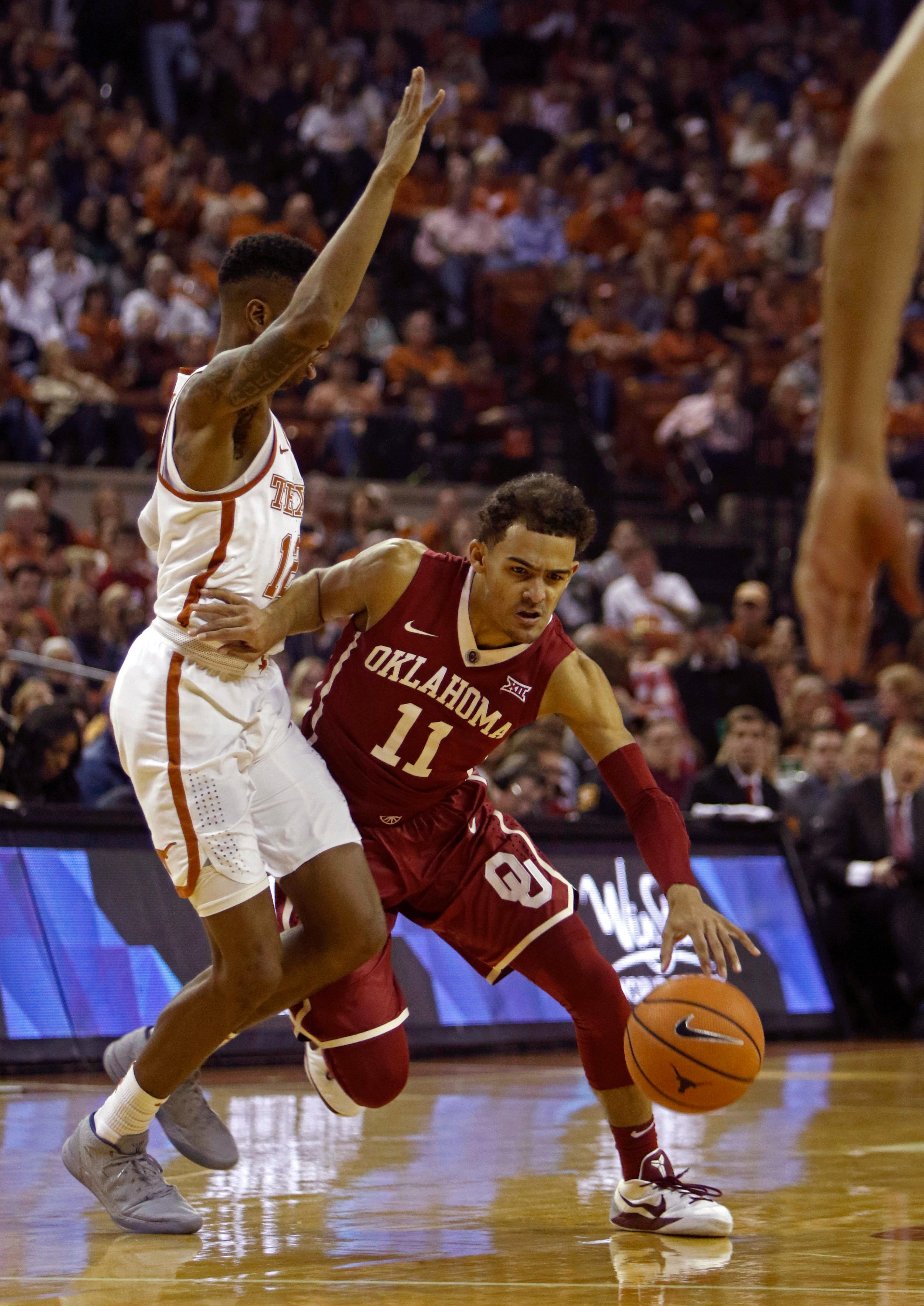 Oklahoma guard Trae Young (11) drives the ball against Texas guard Kerwin Roach II during the first half of an NCAA college basketball game, Saturday, Feb. 3, 2018, in Austin, Texas. (AP Photo/Michael Thomas)