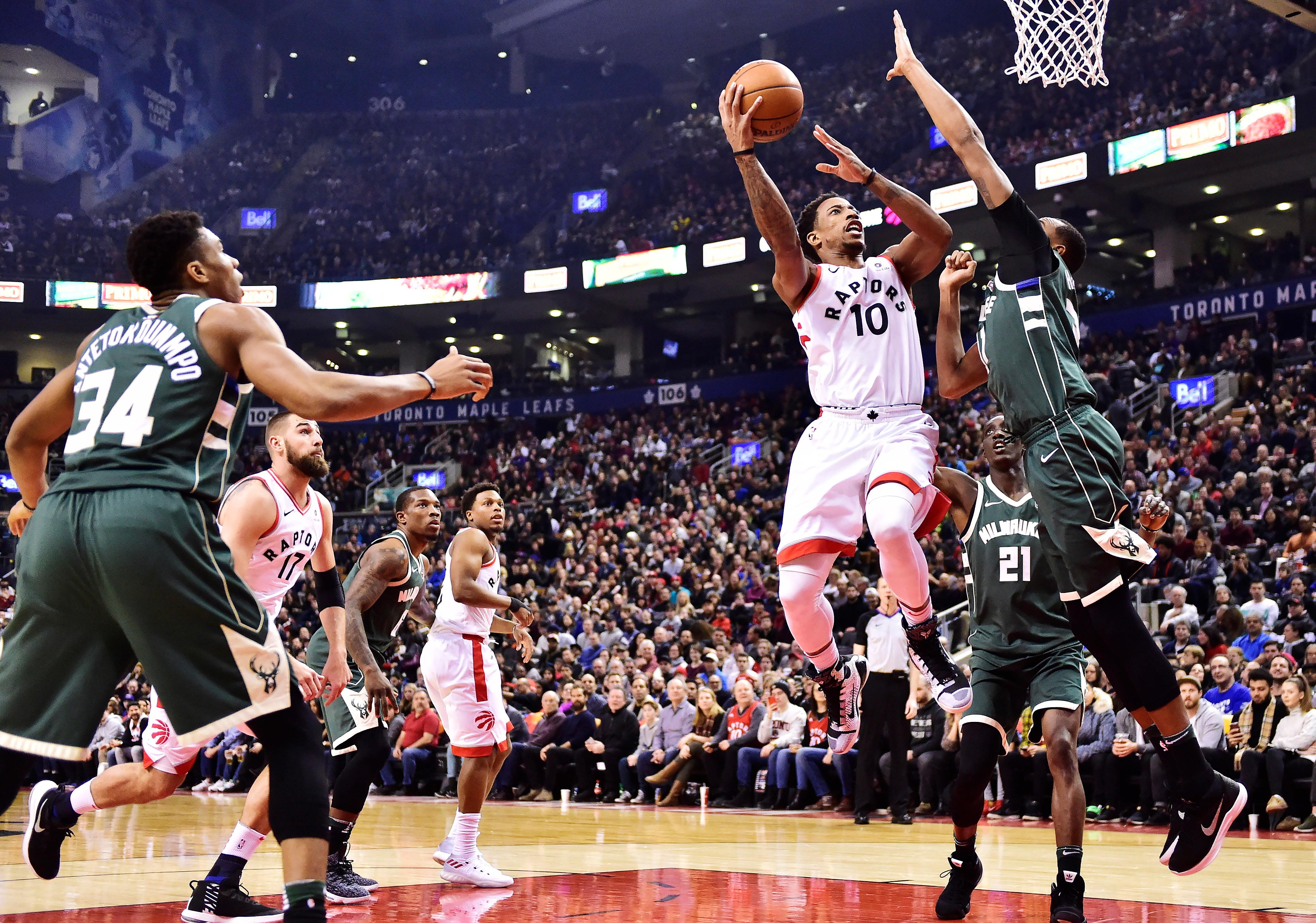 Toronto Raptors guard DeMar DeRozan (10) shoots over Milwaukee Bucks forward John Henson (31) during first half action in Toronto on Monday, Jan. 1, 2018. (Frank Gunn/The Canadian Press via AP)