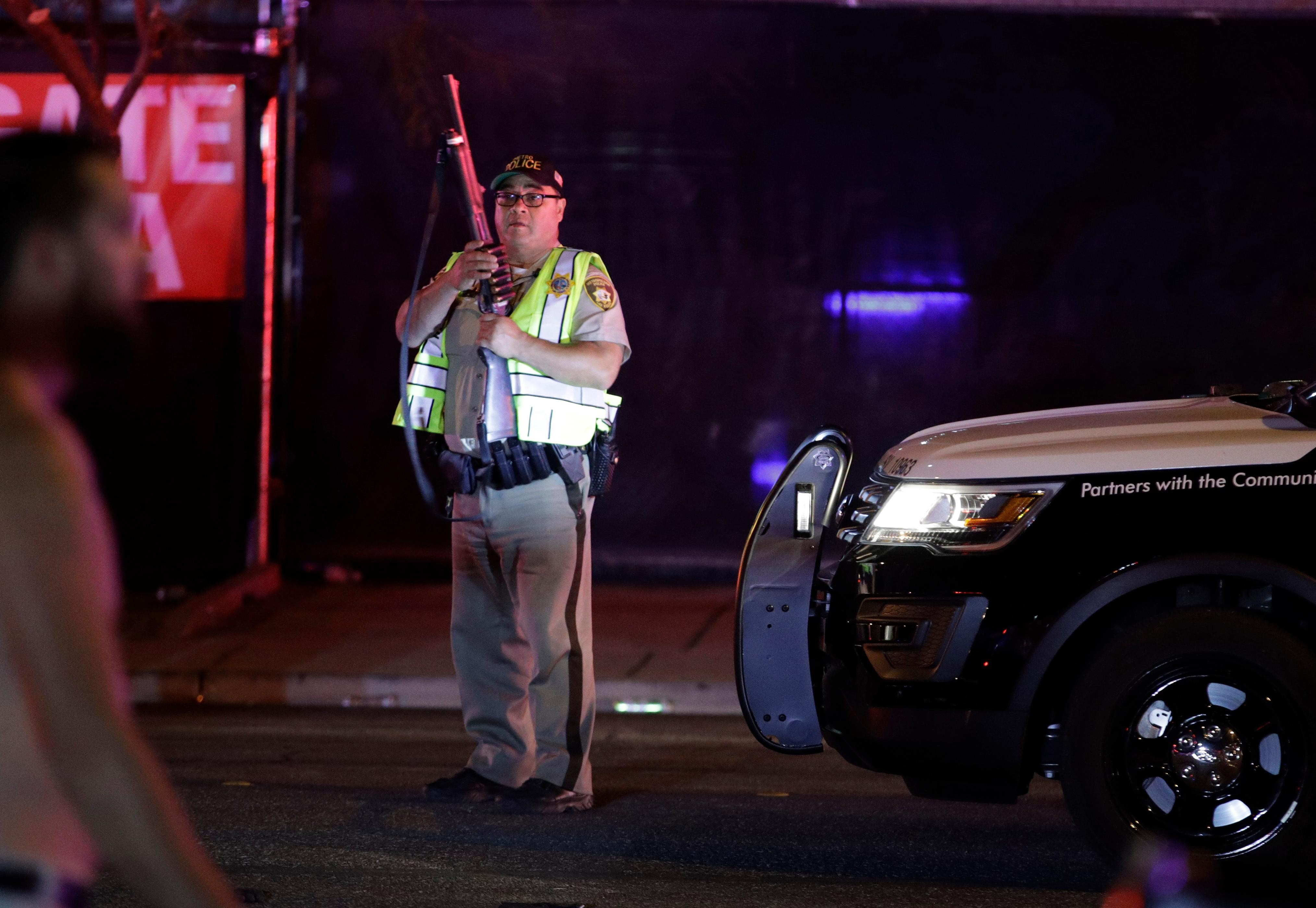 A police officer stands at the scene of a shooting along the Las Vegas Strip, Monday, Oct. 2, 2017, in Las Vegas. Multiple victims were being transported to hospitals after a shooting late Sunday at a music festival on the Las Vegas Strip. (AP Photo/John Locher)