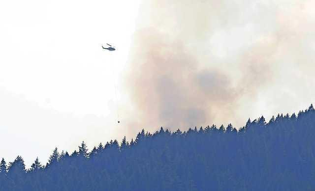 Andy Atkinson / Daily TidingsA helicopter moves into position to make a dump of water on the Wagner Creek fire Monday morning.