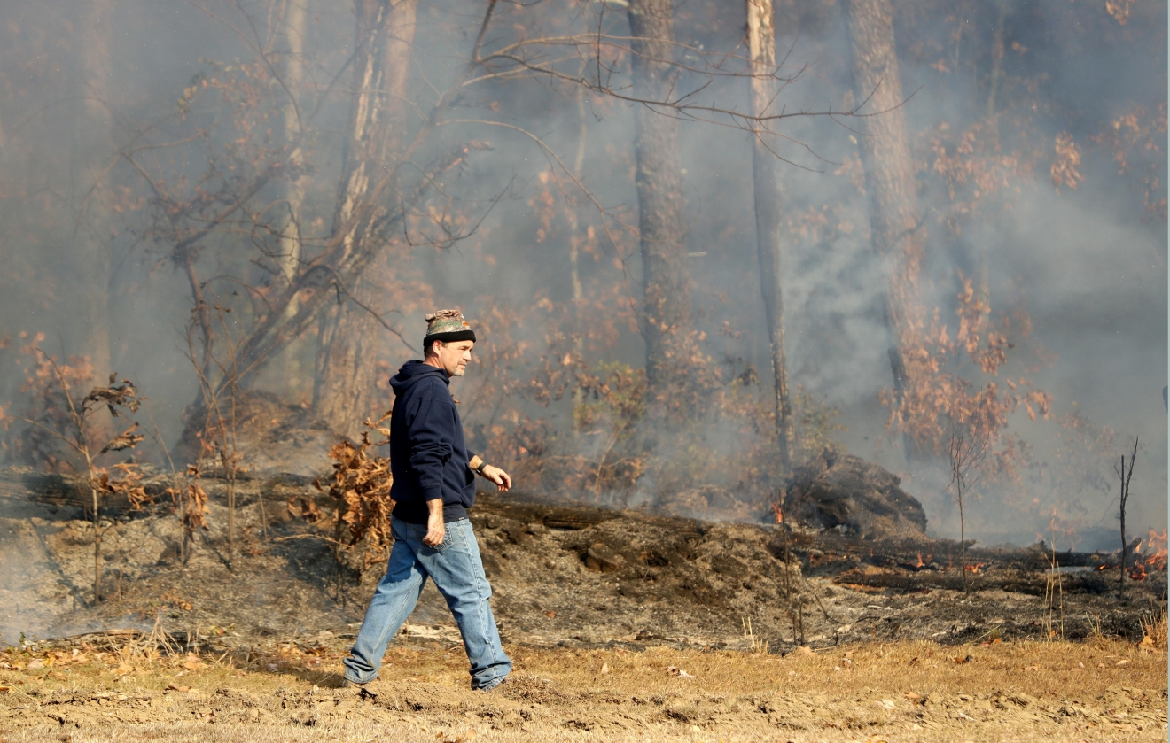 David Benton walks past burning trees and brush at his home Thursday, Nov. 10, 2016, in Soddy-Daisy, Tenn. Benton owns 39 acres and is monitoring the fire to protect his house. Federal authorities say warmer-than-average temperatures and no rainfall are deepening a drought that's sparking forest fires across the Southeastern U.S. (AP Photo/Mark Humphrey)