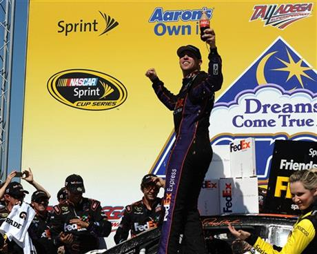 Denny Hamlin celebrates in Victory Lane after winning the NASCAR Aaron's 499 Sprint Cup series auto race at Talladega Superspeedway, Sunday, May 4, 2014, in Talladega, Ala. (AP Photo/Rainier Ehrhardt)