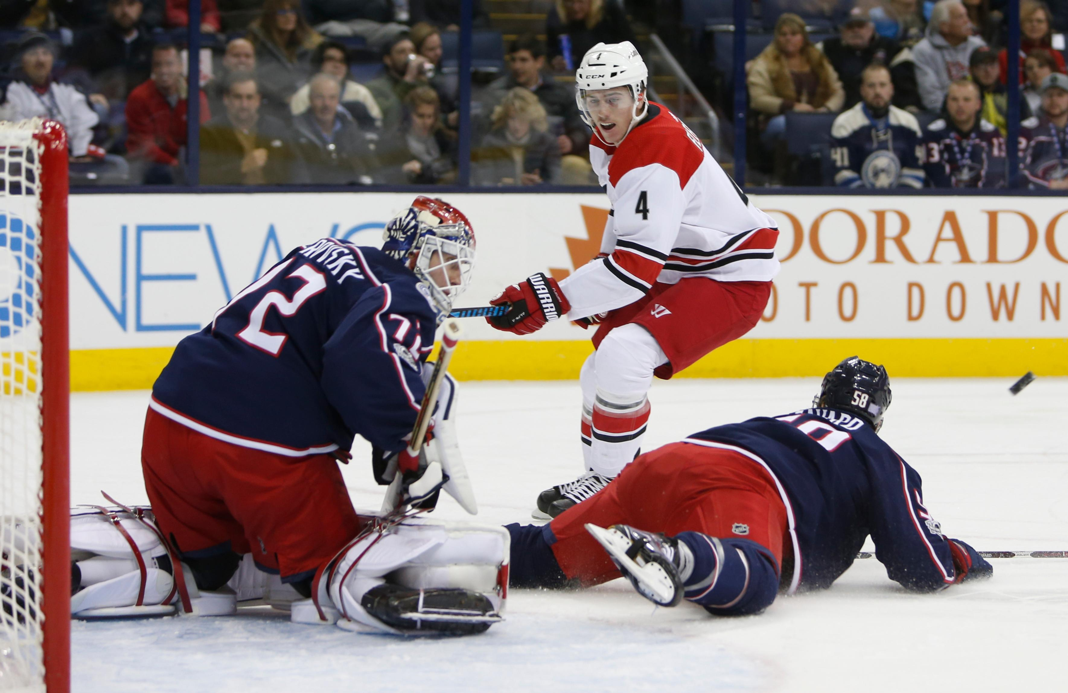 Columbus Blue Jackets' Sergei Bobrovsky, left, of Russia, makes a save as teammate David Savard, right, falls to the ice and Carolina Hurricanes' Haydn Fleury looks for the rebound during the first period of an NHL hockey game Friday, Nov. 10, 2017, in Columbus, Ohio. (AP Photo/Jay LaPrete)