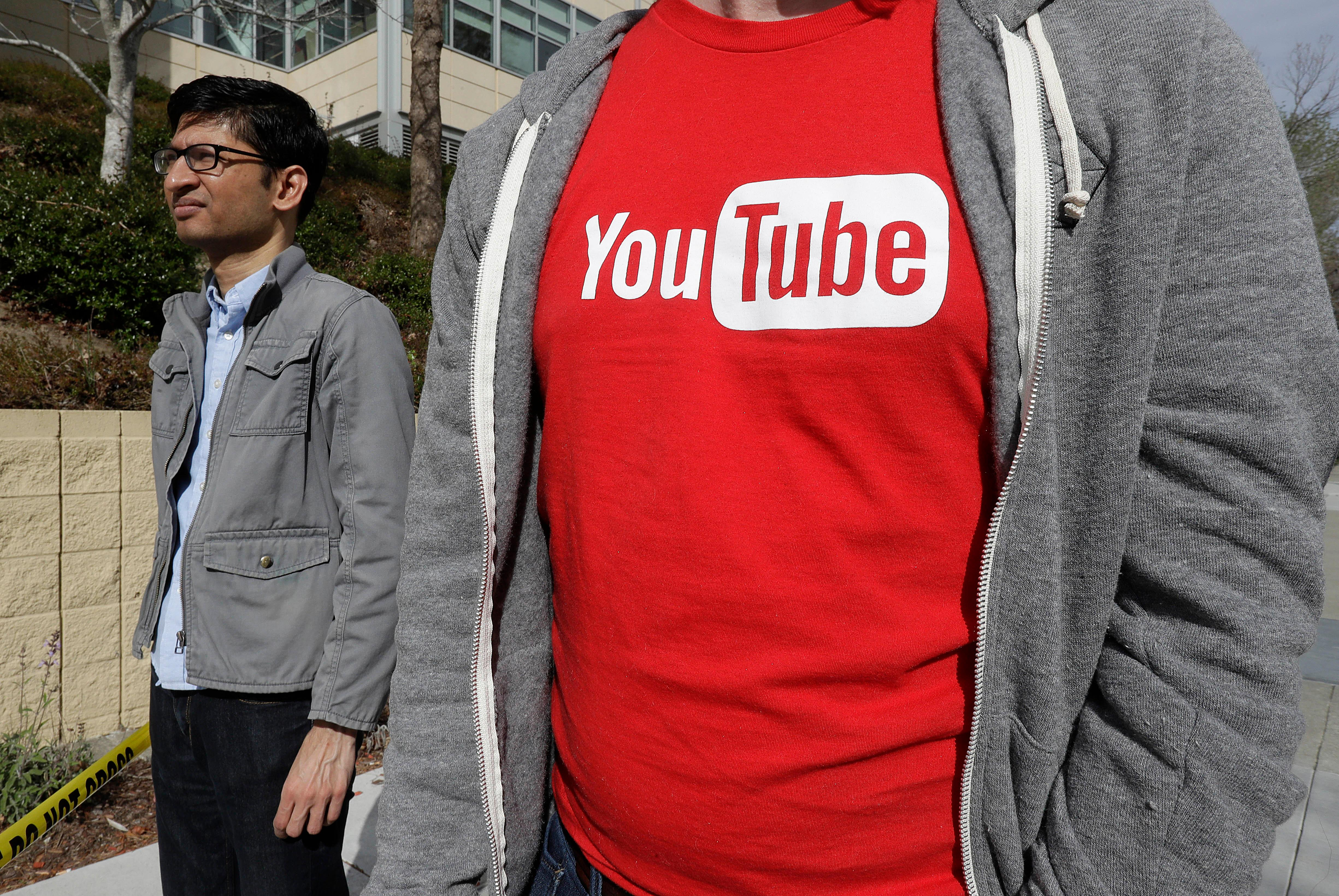 People wait to be escorted into a YouTube office building in San Bruno, Calif., Wednesday, April 4, 2018. A woman suspected of shooting three people at YouTube headquarters before killing herself was furious with the company because it had stopped paying her for videos she posted on the platform, her father said Tuesday, April 3, 2018. (AP Photo/Jeff Chiu)
