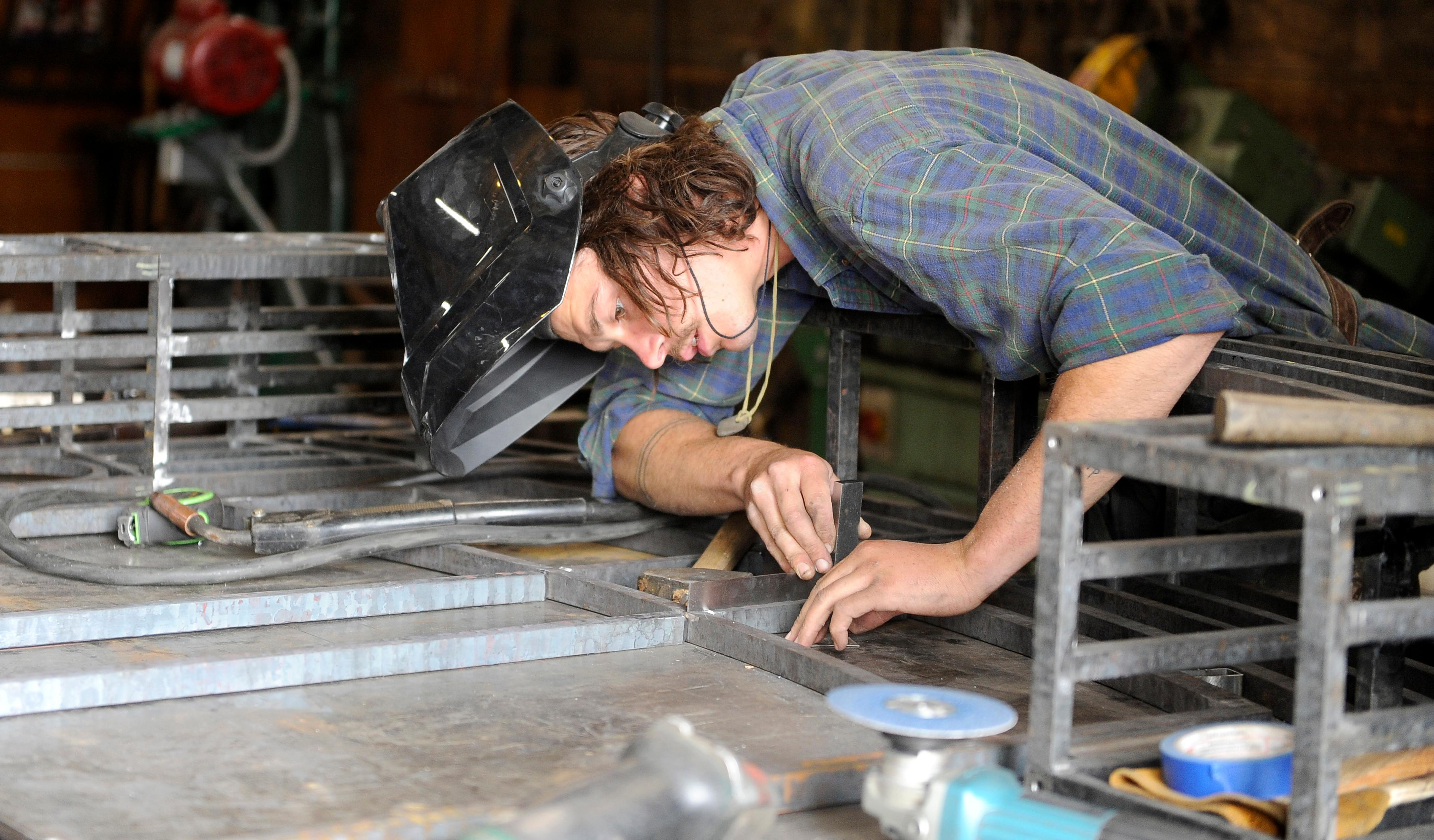 Andy Atkinson / Mail Tribune<br>Drew Phelan works on creating an entry gate for a local resident at Ashland Forge.