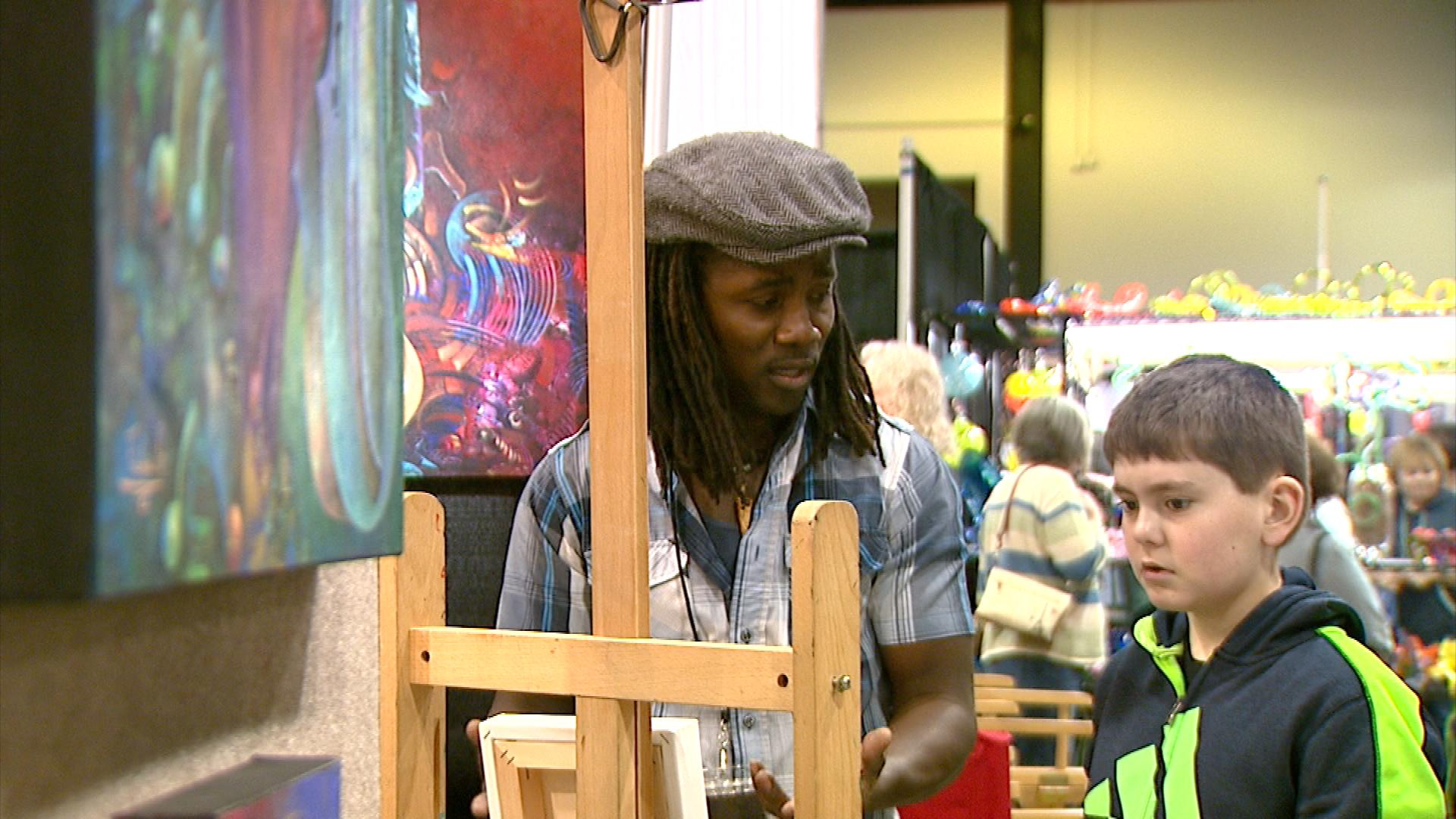 A painter teaches a young boy how to paint on canvas Saturday, March 3, 2018.(WLUK/Jessie Basinski)