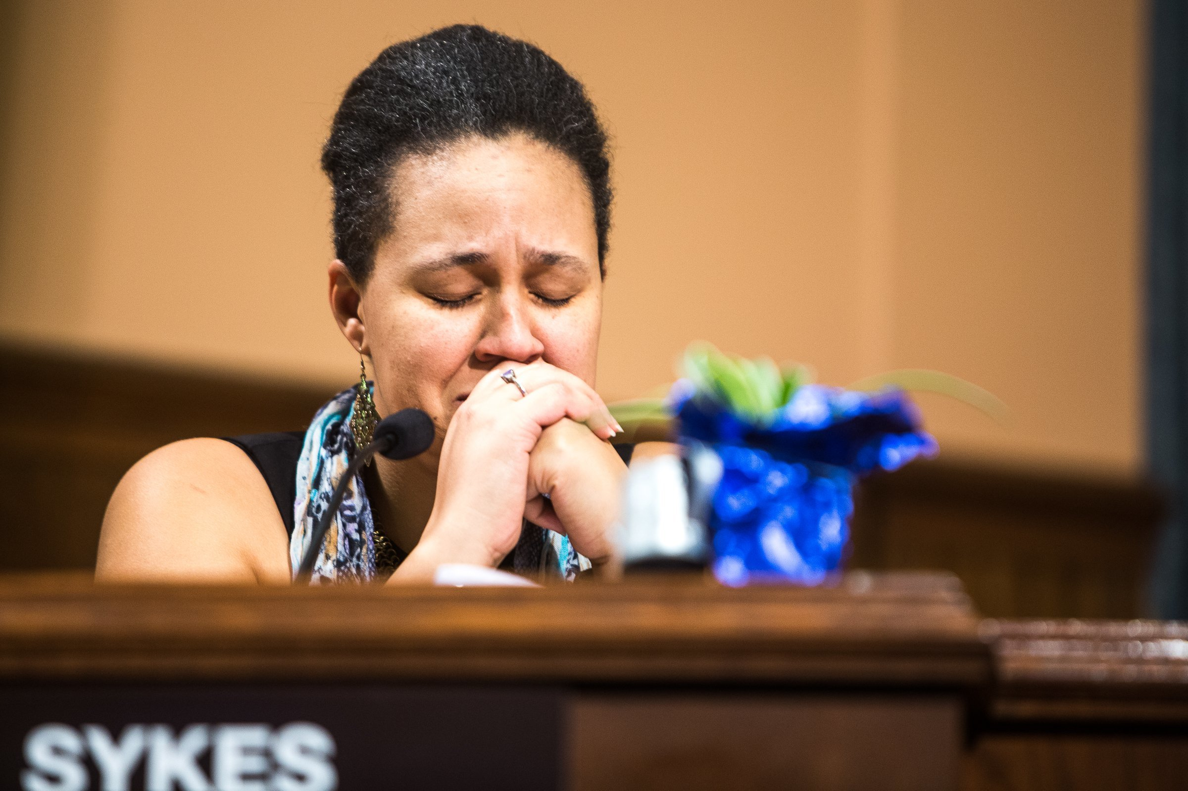Kalamazoo City Commissioner Shannon Sykes closes her eyes as she tears up when Mayor Bobby Hopewell says he will vote in favor of removing the Fountain of the Pioneers from Bronson Park. (Rebekah Welch/Kalamazoo Gazette-MLive Media Group via AP)
