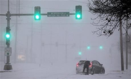 A Crestwood motorist tries to get his car moving along Watson Road in St. Louis as heavy snow falls on Sunday, Jan. 5, 2014.