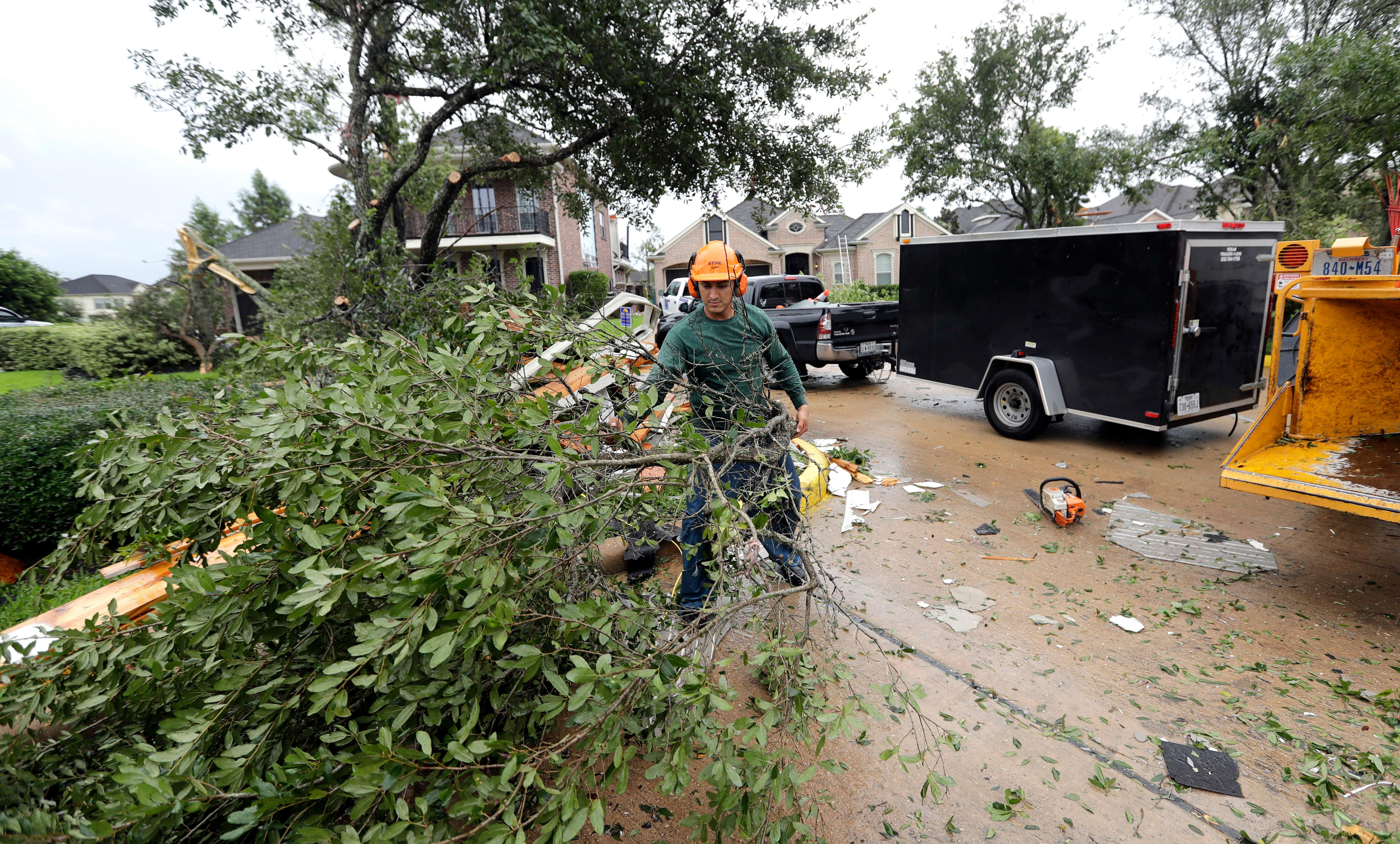 Henry Isaac removes broken tree limbs after Hurricane Harvey Saturday, Aug. 26, 2017, in Missouri City, Texas.  Harvey rolled over the Texas Gulf Coast on Saturday, smashing homes and businesses and lashing the shore with wind and rain so intense that drivers were forced off the road because they could not see in front of them.  (AP Photo/David J. Phillip)