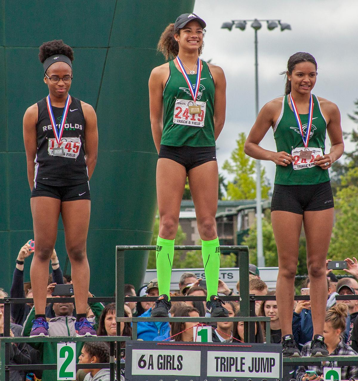 Peace Igbonagwam (left), Taylor McCarrell (middle) and Elea McCrae (right) receive their medals after participating in the Girls Triple Jump 6A event. This event was won by Taylor McCarrell from West Salem High School with the distance of 38-02.25 at the OSAA Track and Field State Championships at Hayward Field. Photo by Vannie Cooper, Oregon News Lab