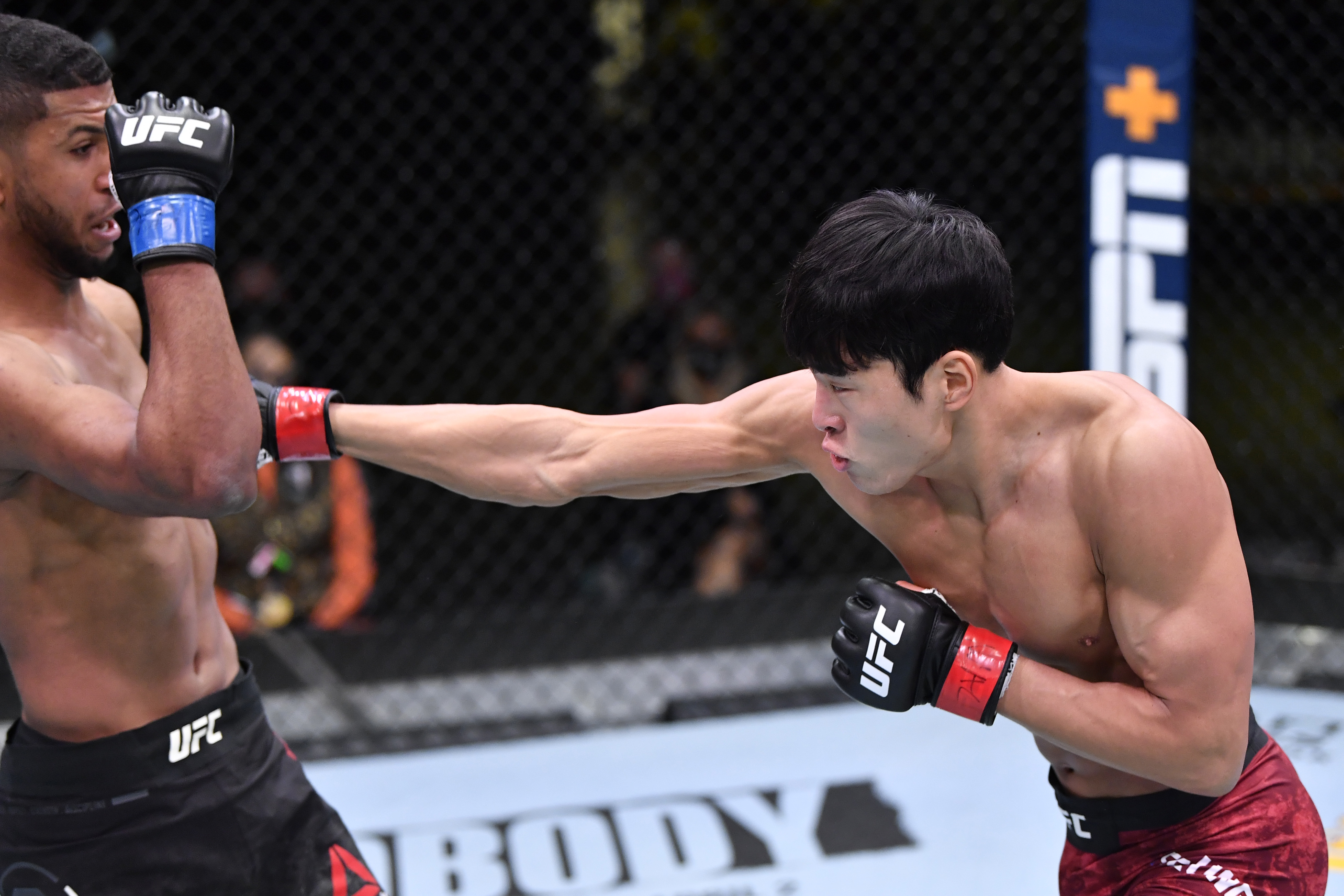 LAS VEGAS, NEVADA - FEBRUARY 06: In this handout image provided by UFC, (R-L) Seungwoo Choi of South Korea punches Youssef Zalal of Morocco in their featherweight fight during the UFC Fight Night event at UFC APEX on February 06, 2021 in Las Vegas, Nevada. (Photo by Chris Unger/Zuffa LLC via Getty Images)