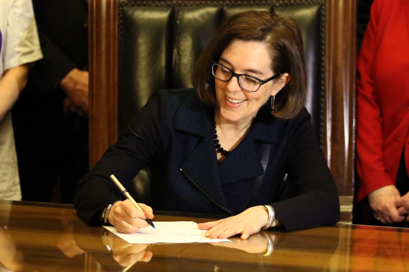 Oregon Gov. Kate Brown signs Senate Bill 1532, increasing Oregon's minimum wage according to a tiered system, at the State Capitol in Salem on Wednesday, March 2, 2016. PortlandÂ?s minimum will rise to $14.75 by 2022, suburban areas to $13.50 and rural areas to $12.50. The tiered approach is based on economic factors.  (Anna Reed/Statesman-Journal via AP) MANDATORY CREDIT
