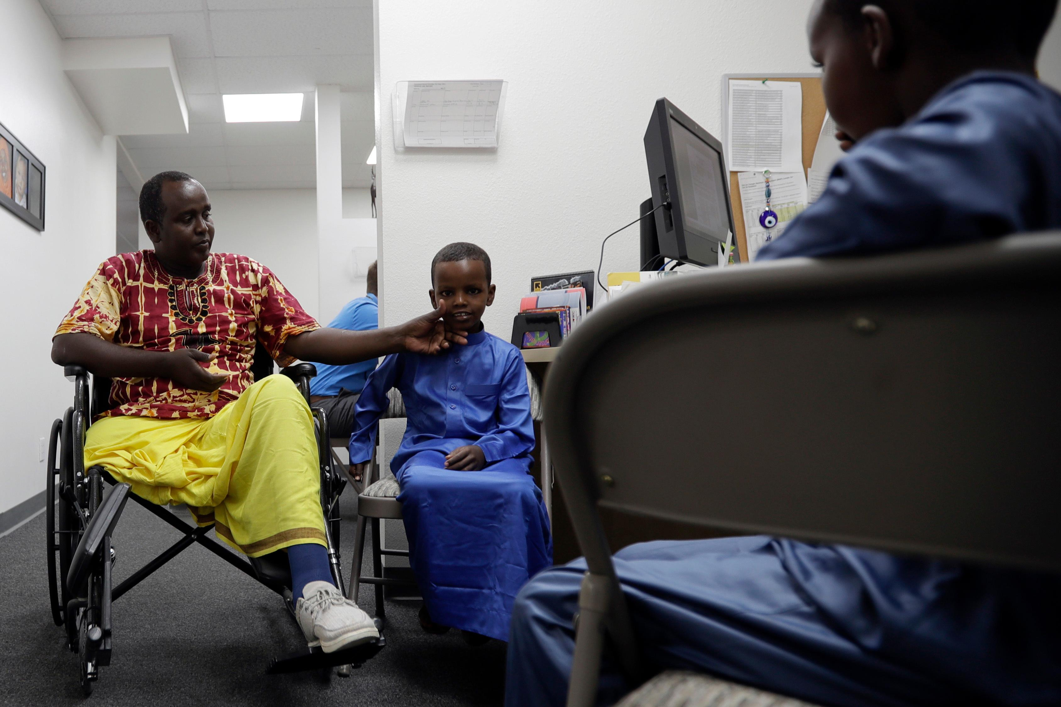 Ali Said, of Somalia, left, waits at a center for refugees with his two sons Thursday, July 6, 2017, in San Diego. Said, whose leg was blown off by a grenade, says he feels unbelievably lucky to be among the last refugees allowed into the United States before stricter rules kick in as part of the Trump administration's travel ban. (AP Photo/Gregory Bull)
